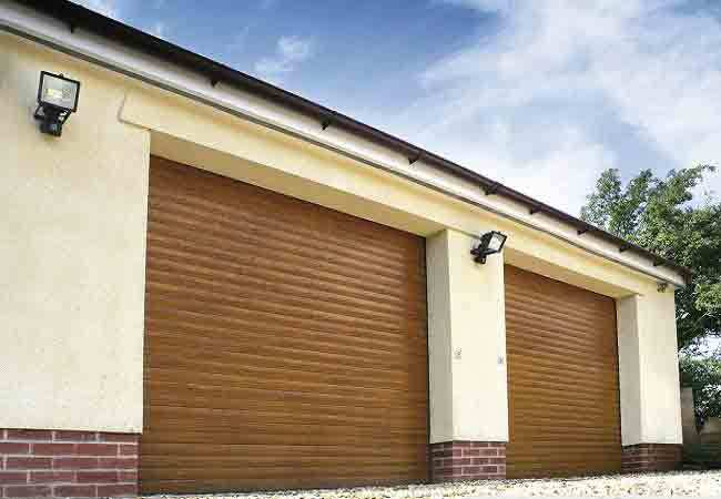 Double garage fitted with 2 x Seceuroglide roller shutter garage doors finished in Golden Oak laminated wood grain