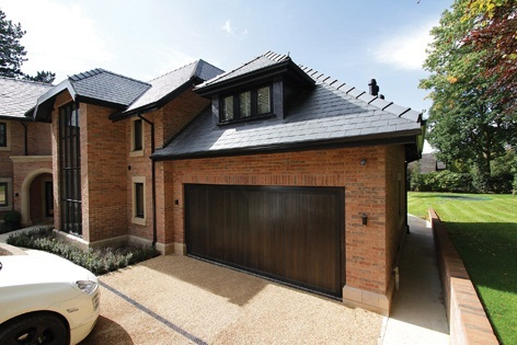 Up & Over wooden garage door fitted to large brick built home with an attached garage